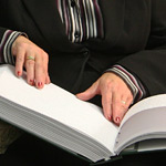 Photo of hands reading a book using Braille